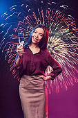 Celebrating new years eve 2021. Vertical shot of a young happy asian woman with glass of champagne standing against fireworks background, smiling at camera