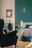 Copy space on empty green wall of elegant bedroom interior