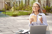 Working online. Portrait of a happy mature business woman wearing eyeglasses having a lunch, drinking coffee and eating sandwich while working outdoors, using laptop