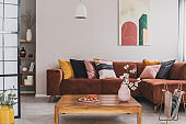 Real photo of a square, wooden table standing in front of a brown, suede sofa with decorative cushions in cozy living room interior