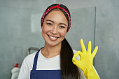 Cleaned right. Close up portrait of joyful young woman wearing yellow gloves, smiling and showing OK sign while cleaning the house
