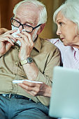 Sick elderly man checking temperature while his wife supporting him