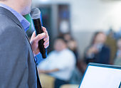 Conference photo audience and speaker giving speech. Seminar presenter on a panel during forum. Corporate manager in sales executive training discussion on stage. Investor pitch presentation.