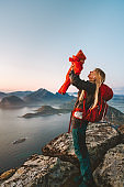 Mother holding up baby traveling hiking in mountains family healthy lifestyle mom with backpack gear and child active vacations outdoor in Norway Lofoten islands