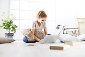 young woman sitting in living room at the computer, stay at home concept