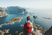 Man sitting on cliff edge alone enjoying aerial view backpacking lifestyle travel adventure outdoor summer vacations in Norway top of Reinebringen mountain