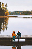 Couple friends traveling in Finland family lifestyle love relationship man and woman sitting talking on pier outdoor lake and autumn season forest landscape