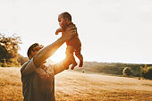 Happy father holding up infant baby outdoor Fathers day holiday family lifestyle dad and child summer vacations together parenthood concept