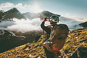Backpacker woman hands showing heart shape enjoying mountains clouds landscape Travel lifestyle adventure concept summer vacations wanderlust outdoor