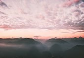 Sunset clouds sky and mountains range landscape travel nature background awesome idyllic evening scenery aerial view