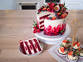 Big beautiful red velvet cake, with flowers and berries on top. Slice on a plate, dessert.