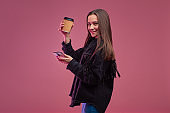Cheerful and smiling young brunette woman with coffee to go, uses a smartphone,