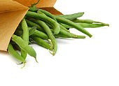 small and slender green beans (haricot vert) in brown paper on a white background