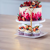 Big beautiful red velvet cake, with flowers and berries on top. Delicious sweet muffins with cream,