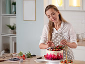 cooking and decoration of cake with cream. Young woman pastry chef in the kitchen decorating red velvet cake