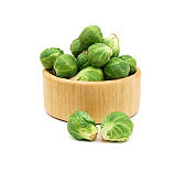 freshly brussel sprouts and some whole ones in wood bowl on a white background