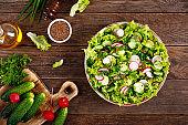 Fresh vegan vegetable salad of radish, cucumbers, lettuce, dill and green onion, healthy vegetarian food