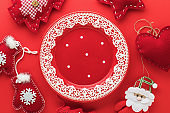 Empty plate and christmas toys on a red background, top view. Food background