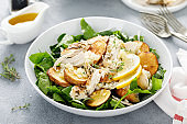 Chicken salad with spinach and crispy potatoes dressed with olive oil, garlic, lemon, onion and thyme