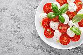 Caprese salad. Salad with mozzarella cheese fresh tomatoes, basil leaves and olive oil. Italian food