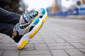 Feet shod in sneakers multi-colored yellow, white, black and blue are on the asphalt road. Close-up