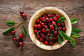 Sweet cherry with leaves in wooden bowl. Fresh ripe cherries. Cherry fruit