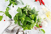 Bunch of aromatic herbs in mortar on kitchen table