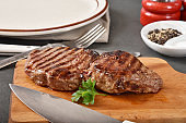A fresh, juicy, grilled beef sirloin steak on a cutting board