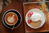 Coffee and strawberry cream cake on wooden table