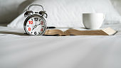 Alarm clock, book, cup of coffee and accessories on white bedding sheets with copy space. Morning lifestyle concept.