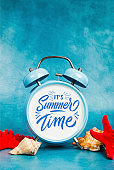 Alarm clock on a blue background with a seashells and starfish