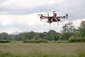 Hex copter camera drone hovers in front of a rural background.
