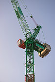 Vertical telephoto close up of a green and orange crane at sunrise