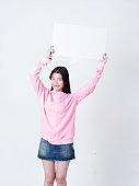 Cheerful girl smiling at camera and showing placard empty.