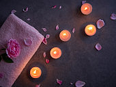 Spa composition of pink rose and candles on grey background.