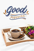 Fresh morning coffee on a board on a bed sheet with text Good Morning