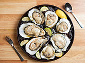 Close-up Of Fresh Oysters On Ice And Lemon In Tray On Wooden Table.