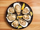 Oysters on ice and lemon in a tray on wooden table