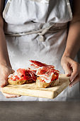 Woman holding wooden try with toasted bread slice with fresh tomatoes and cured ham. Delicious appetiser Italian prosciutto and Spanish Iberian ham snack