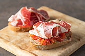 Crusty toast with fresh tomatoes and cured ham. Delicious appetiser Italian prosciutto and Spanish Iberian ham snack