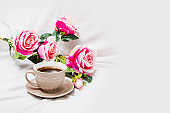 Black coffee with pink roses on a white sheet