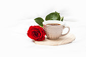 Black coffee with red rose on a white sheet