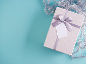 Gifts box against greeting card on light blue background.