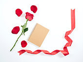 Red rose with red ribbon on a diary. Love symbol. For card and wedding.