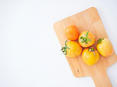 Top view of tomatoes with wooden cutting board on white background. Space for text