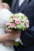 Unrecognizable bride and groom with wedding bouquet of red roses