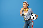 Shoked young woman with yellow penny or skateboard, soccer ball and headphones over blue background.