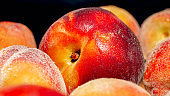 Macro photo of wet peaches and apricots over black backgorund. Abstract background of seasonal fruits