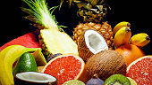 Beautiful background with fresh cut tropical exotic fruits over black backgorund