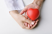 Love and healthcare concepts, Red heart in hands, Doctor holding senior patient hand to giving support, Organ donate and health charity.